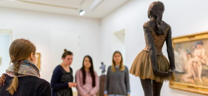 A woman with a plaited braid explains three other women's works of art. They are looking at the sculpture of a dancer.