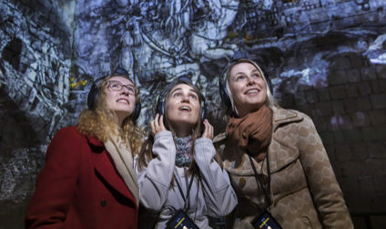 Three women with headphones listen to the story of Dresden Fortress.