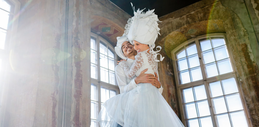 Young wedding couple in white, baroque clothing embraces each other with great joy