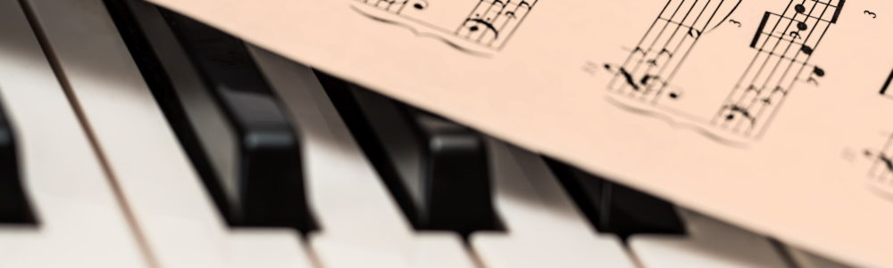 Sheet music on half covered piano keys